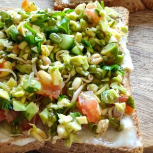 One brown bread toast topped with mashed avocado, sprouts, chopped cucumber, and tomatoes