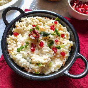 curd rice garnished with pomegranate seeds served in a black wok kept on a red table napkin
