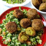 Vegan snack falafel served over Tabbouleh on a red plate with more salad and falafel in the background