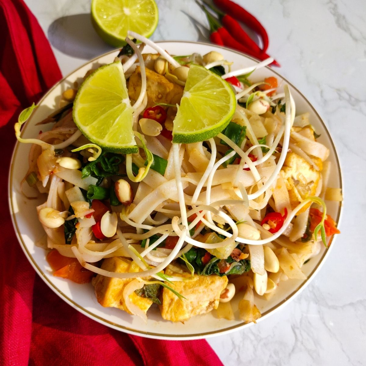 Vegan Pad Thai served in a white bowl garnished with lime wedges