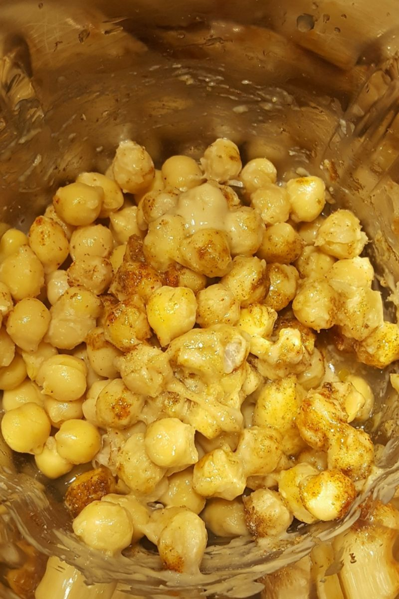 Chickpeas, tahini and other hummus ingredients inside a mixing jar