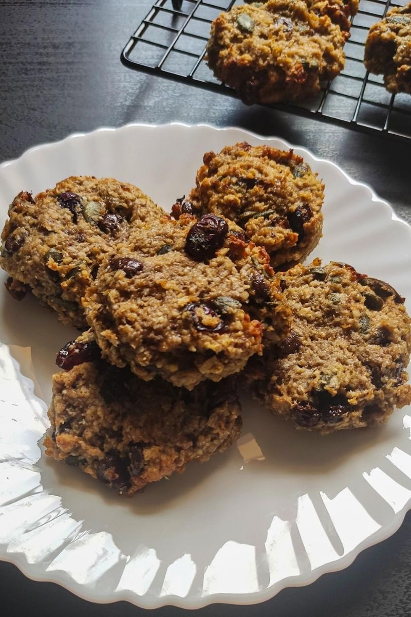 Vegan breakfast cookies on a white plate more cookies in the background