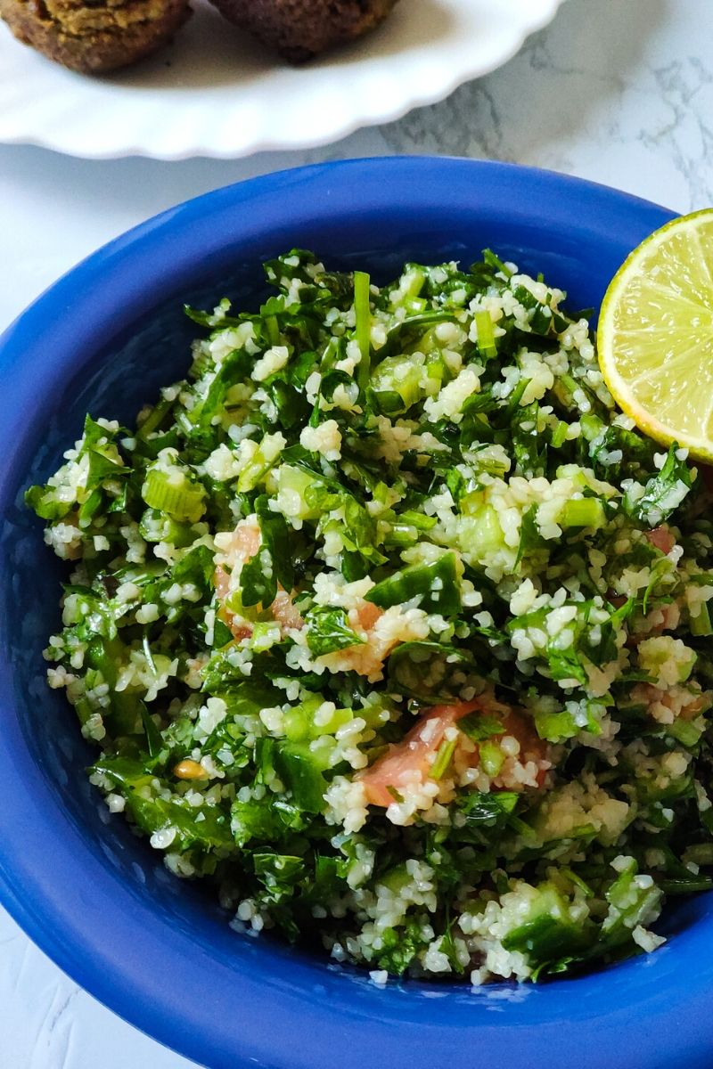 Middle Eastern Salad Tabbouleh serve in a blue bowl with a lime wedge on top