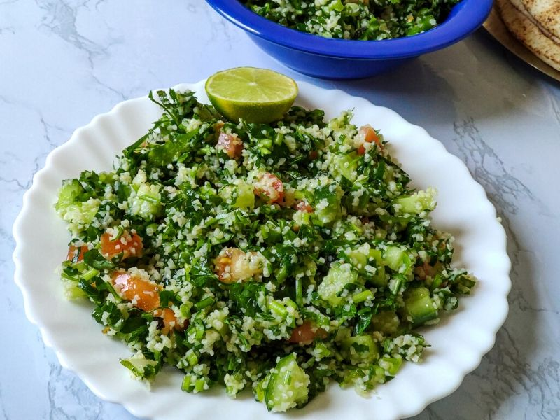 Middle Eastern Salad Tabbouleh serve on a white plate with a lime wedge on top another blue bowl of salad in the background