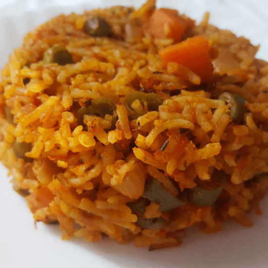African dish jollof rice with green peas, beans and carrots served on a white plate