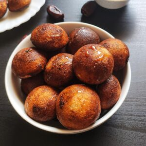 Sweet paniyaram served in a white bowl with some dates and paniyaram in the background