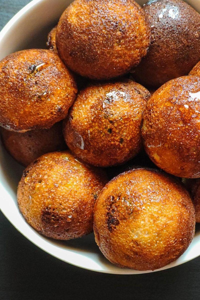 close up shot of sweet paniyarams in a white bowl