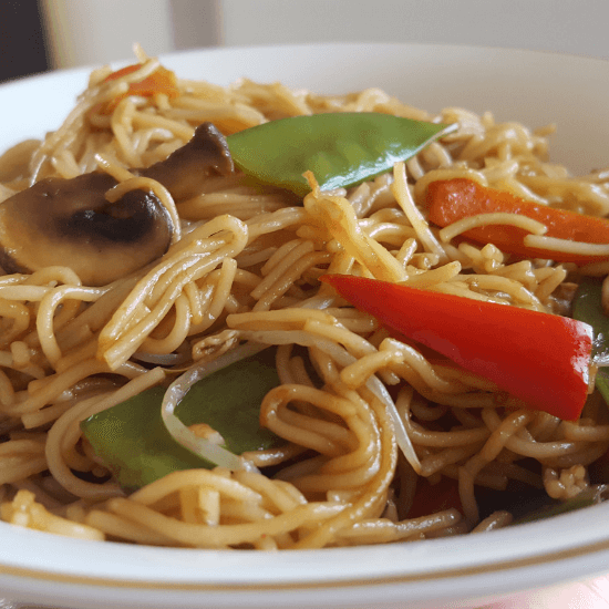 Vegetable Teriyaki Noodles with mushrooms, red bell pepper, and snow peas served in a white bowl
