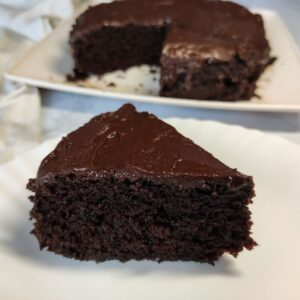 a slice of vegan chocolate cake with thicker layer of chocolate glaze, served on a white plate. Remaining cake in the background.