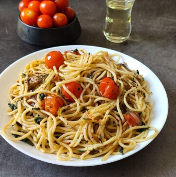 Cherry tomato pasta served in a white plate with a bowl of tomatoes and olive oil in the background