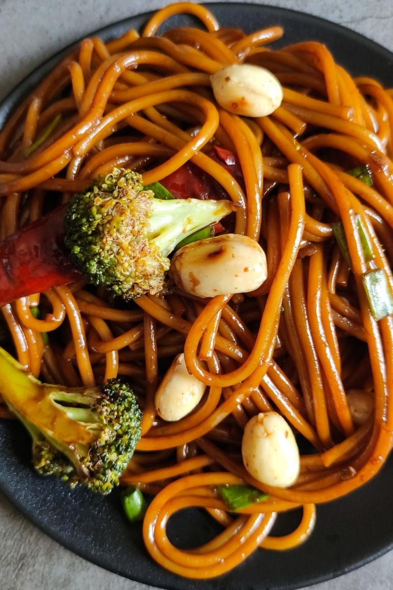 Close up shot of kung pao noodles on a black plate