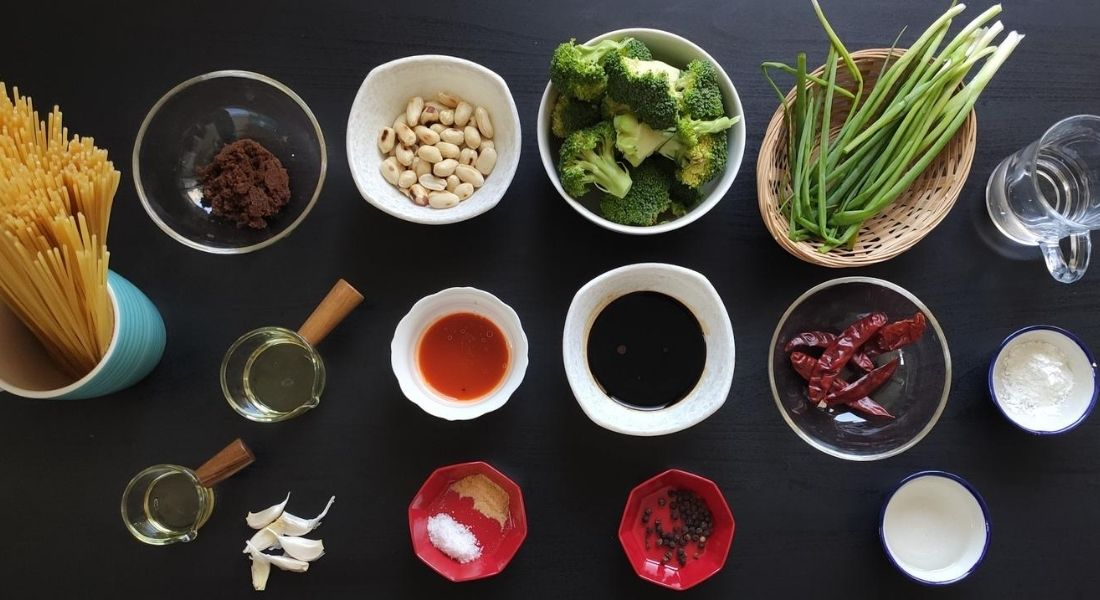 ingredients for vegan kung pao noodles on a black board
