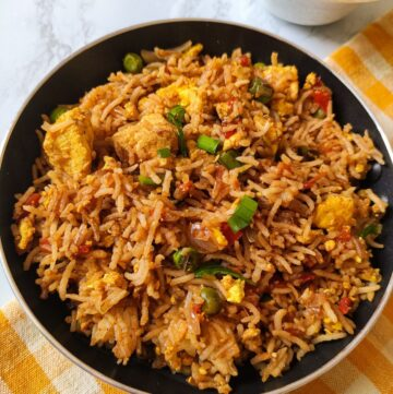 tofu fried rice served in a black pan kept on a table napkin with yellow and white checks