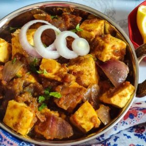 Paneer do pyaza garnished with onion rings served in a bowl