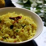 lemon rice served in a white bowl with curry leaves and lemon in the background