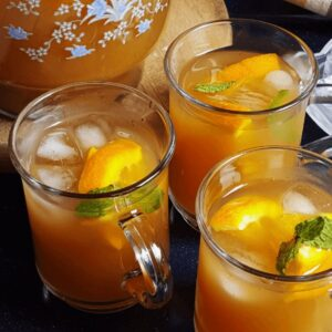 orange iced tea served in three glasses and a pitcher