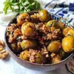 Persian style green marinated olives served in a bowl with mint leaves in the background