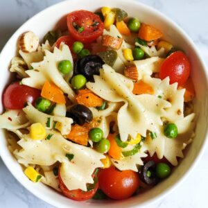 Easy vegan pasta salad made with farfalle, cherry tomatoes, and vegetables.