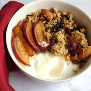 a bowl with home made granola, yogurt, and fresh cut plums
