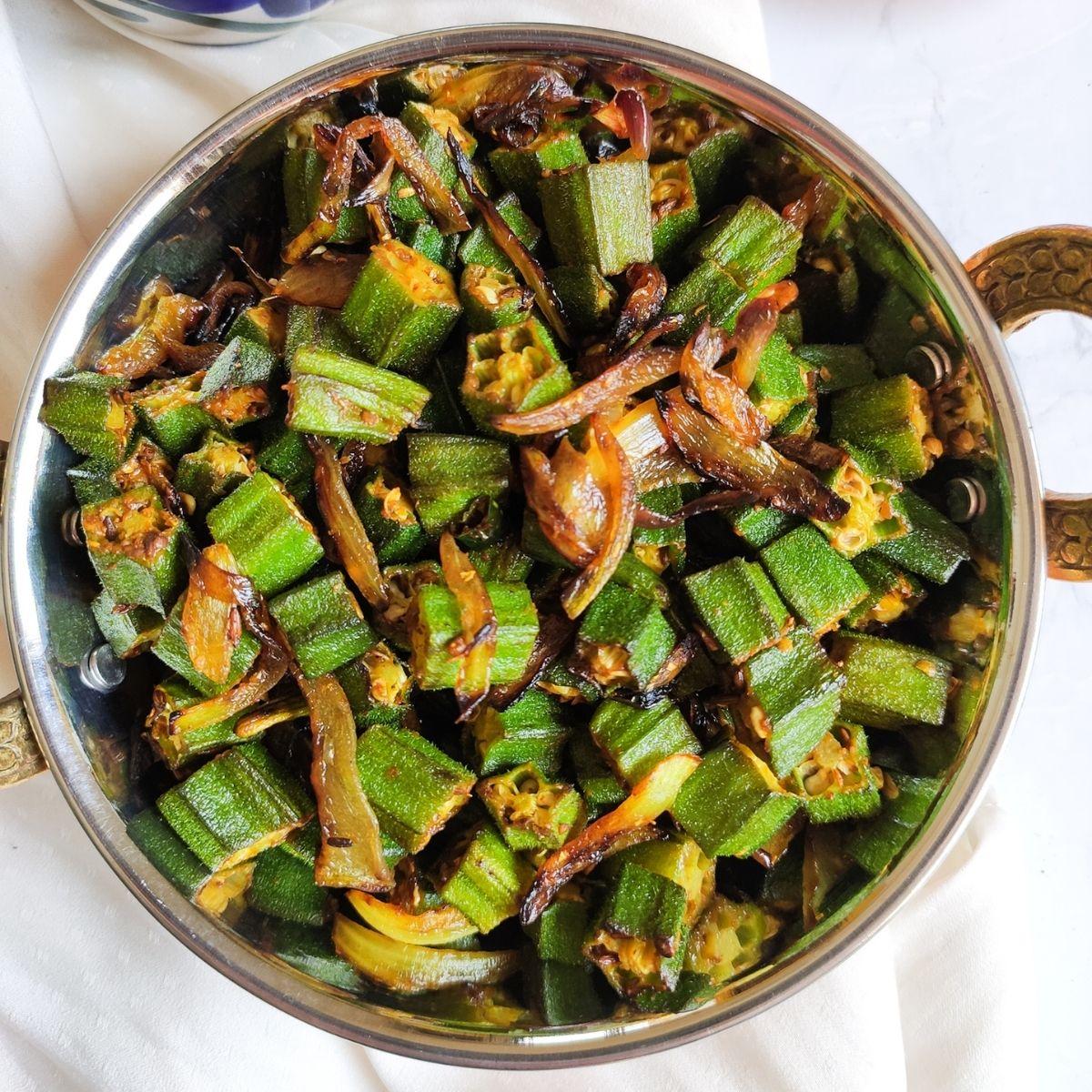 bhindi ki sabzi i.e. okra cooked with onions served in a copper wok