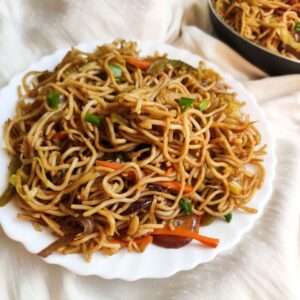 Veg chow mein made with noodles and vegetables served in a white plate