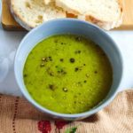 Green peas soup served in a grey bowl with bread slices