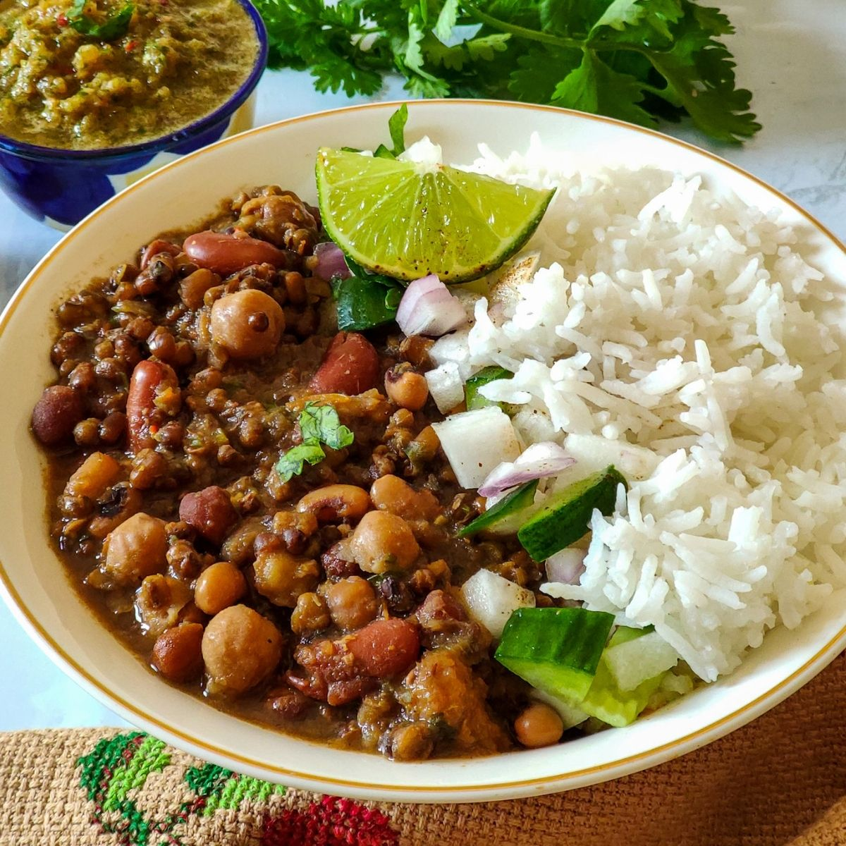 Mixed Indian beans curry and rice served in a white bowl with lime wedges and chutney
