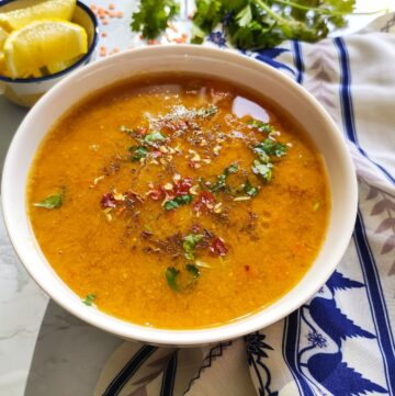 Lebanese lentil soup served in a white bowl with some lime wedges, raw red lentil and coriander leaves in the background