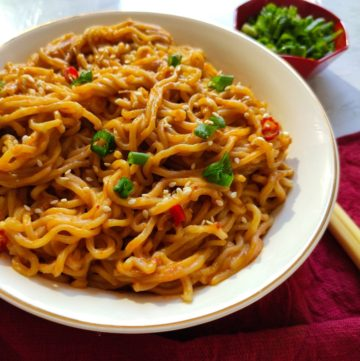 hot peanut butter noodles garnished with spring onion, chilies, and sesame seeds served in a white bowl with red chopsticks