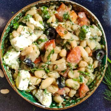 Mediterranean white bean salad served in a green bowl with fresh dill and dried white beans in the background
