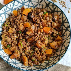 Vegan lentil salad Mshosh served in a white and grey ceramic bowl kept on a grey napkin