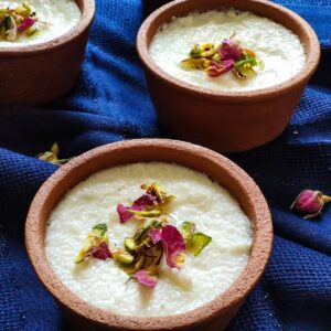 Indian rice pudding phirni garnished with dried rose petals, pistachio, and saffron served in two clay bowls kept on a blue table cloth