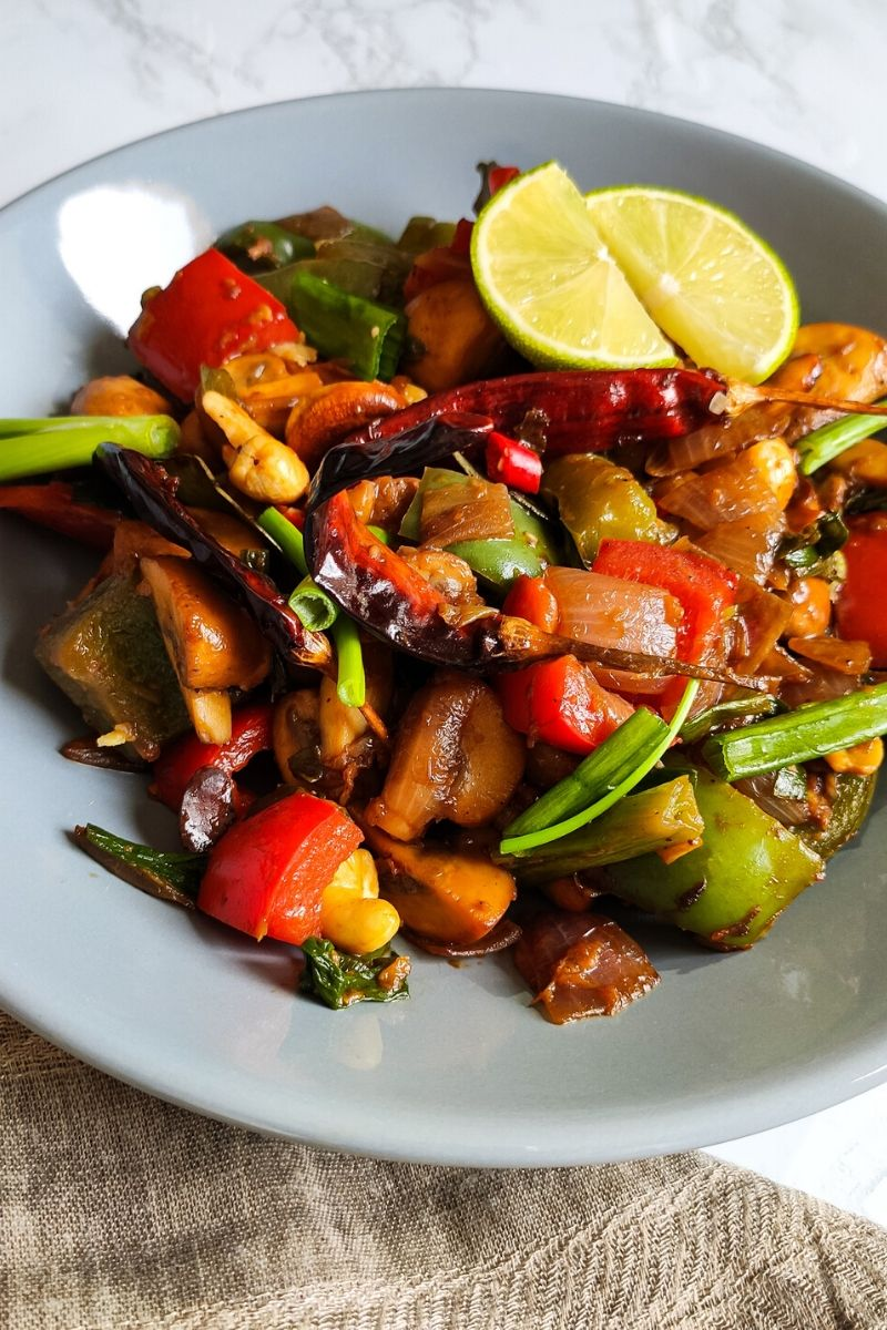 Stir fried Thai mushrooms garnished with dried red chilies, spring onion, and lime wedges served in a grey bowl
