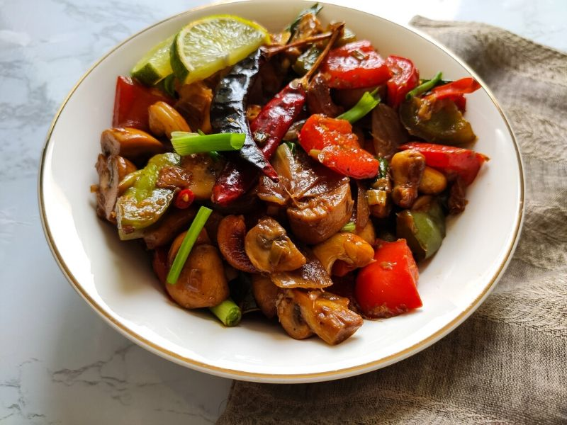 Stir fried Thai mushrooms garnished with dried red chilies, spring onion, and lime wedges served in a white bowl