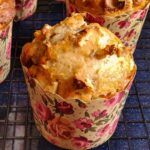 Vegan banana muffin in a floral paper muffin mold kept on a cooling rack and more muffins in the background