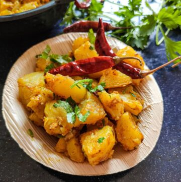 Pan fried potatoes garnished with fried chilies and coriander leaves served in a small wooden bowl