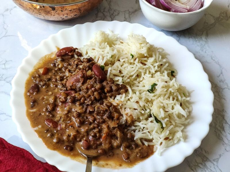 Dal makhani served with rice on a white plate