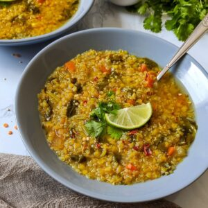 Lentil quinoa soup garnished with fresh coriander leaves and a lime wedge, served in a grey bowl with a spoon.