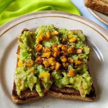 vegan avocado toast with pineapple and sweetcorn served on a plate kept on a bright green table napkin
