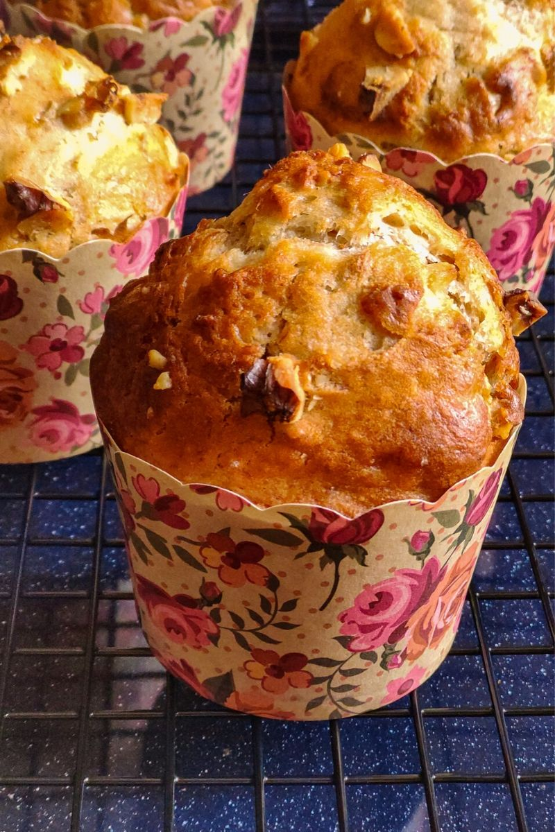 Vegan banana muffins in floral paper muffin molds kept on a cooling rack