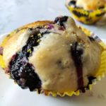 One vegan blueberry muffin in a yellow paper cup another muffin in the back ground