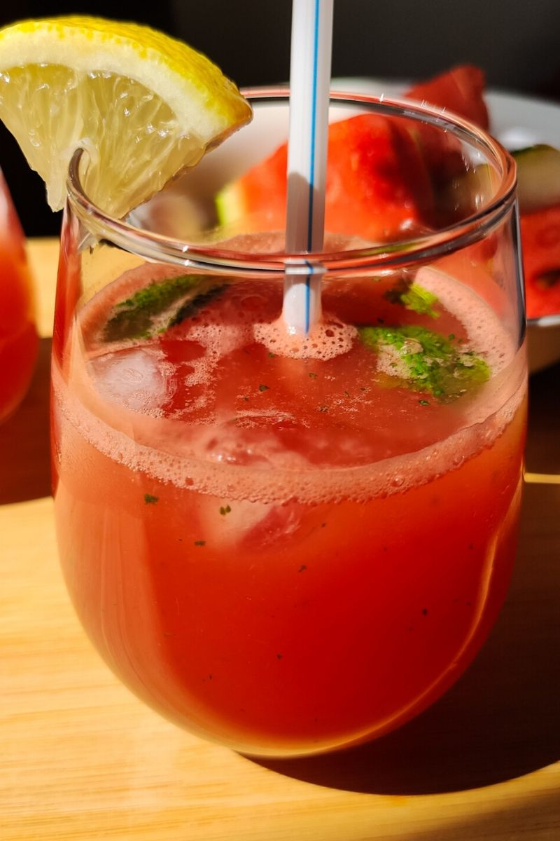 watermelon lemonade served in glass with a white straw and garnished with mint leaves and a lemon wedge.