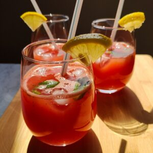 Three glasses of watermelon lemonade with white straws, garnished with mint leaves and lemon wedges