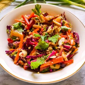 Thai cabbage salad served in a white bowl with some spring onion stalks in the background
