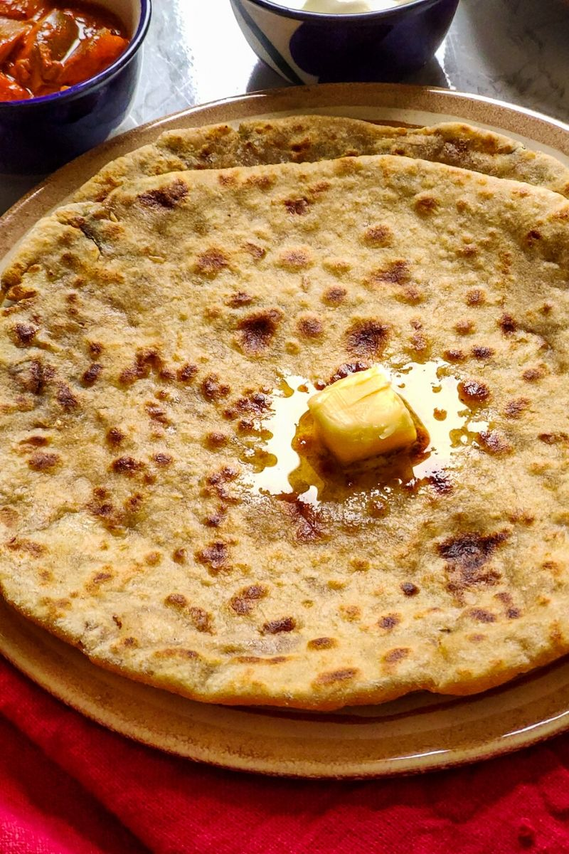 2 aloo parathas on top of each other topped with a butter cube served on a light brown plate with pickle and yogurt in the background