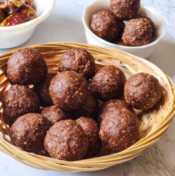 chocolate energy balls kept in a cane basket with some chocolate balls and dates in the background