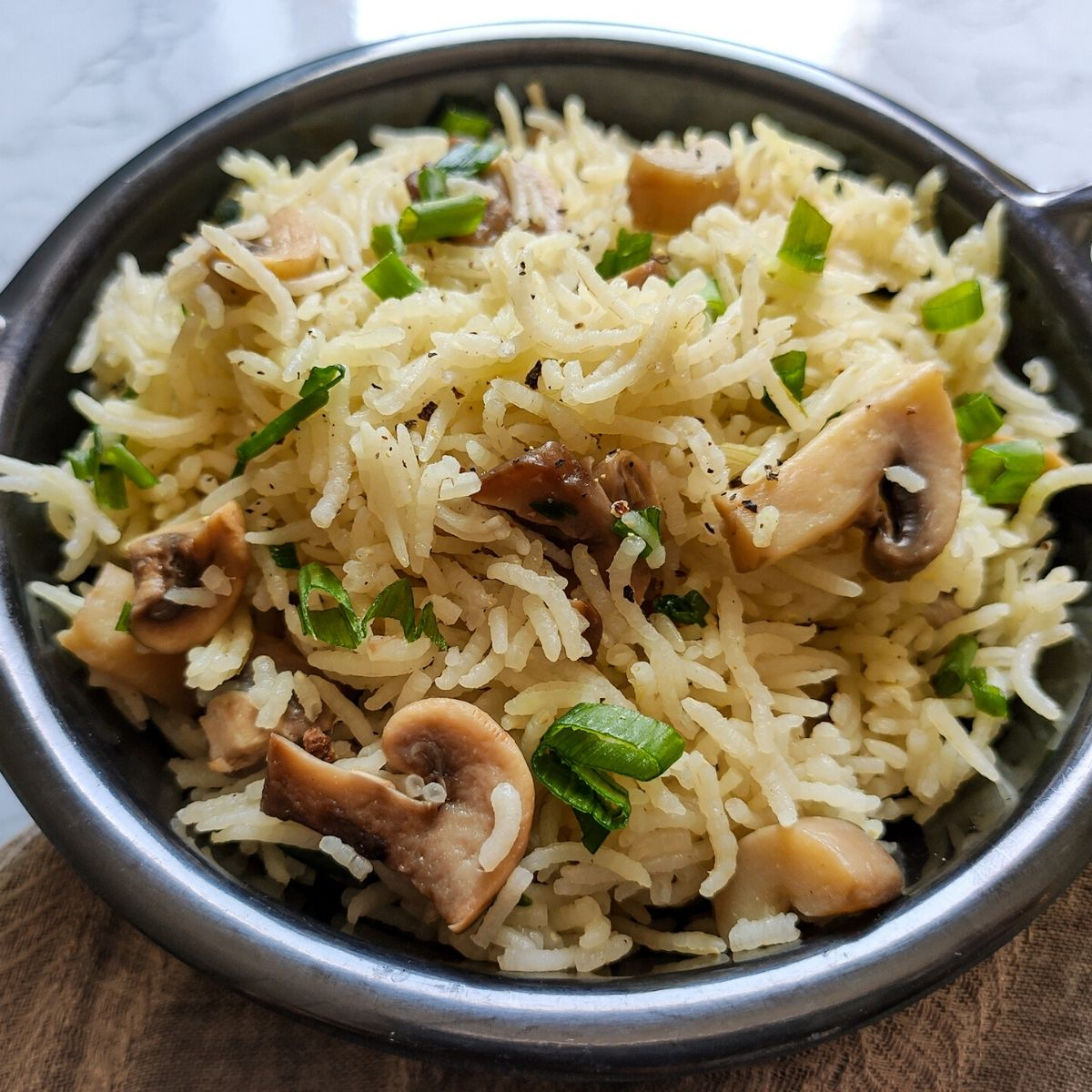 Mushroom rice garnished with chopped spring onion served on a black wok