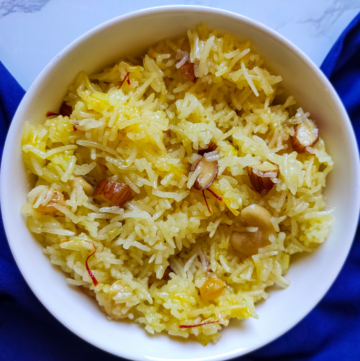 Indian style sweet rice garnished with dry fruits served in a white bowl kept on a blue table napkin