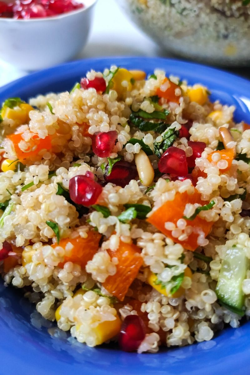 quinoa salad served in a blue bowl and some pomegranate seeds kept in a white bowl in the background