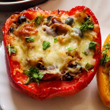 one piece of stuffed red bell pepper kept on a white plate and a small portion of yellow bell pepper also visible on the side